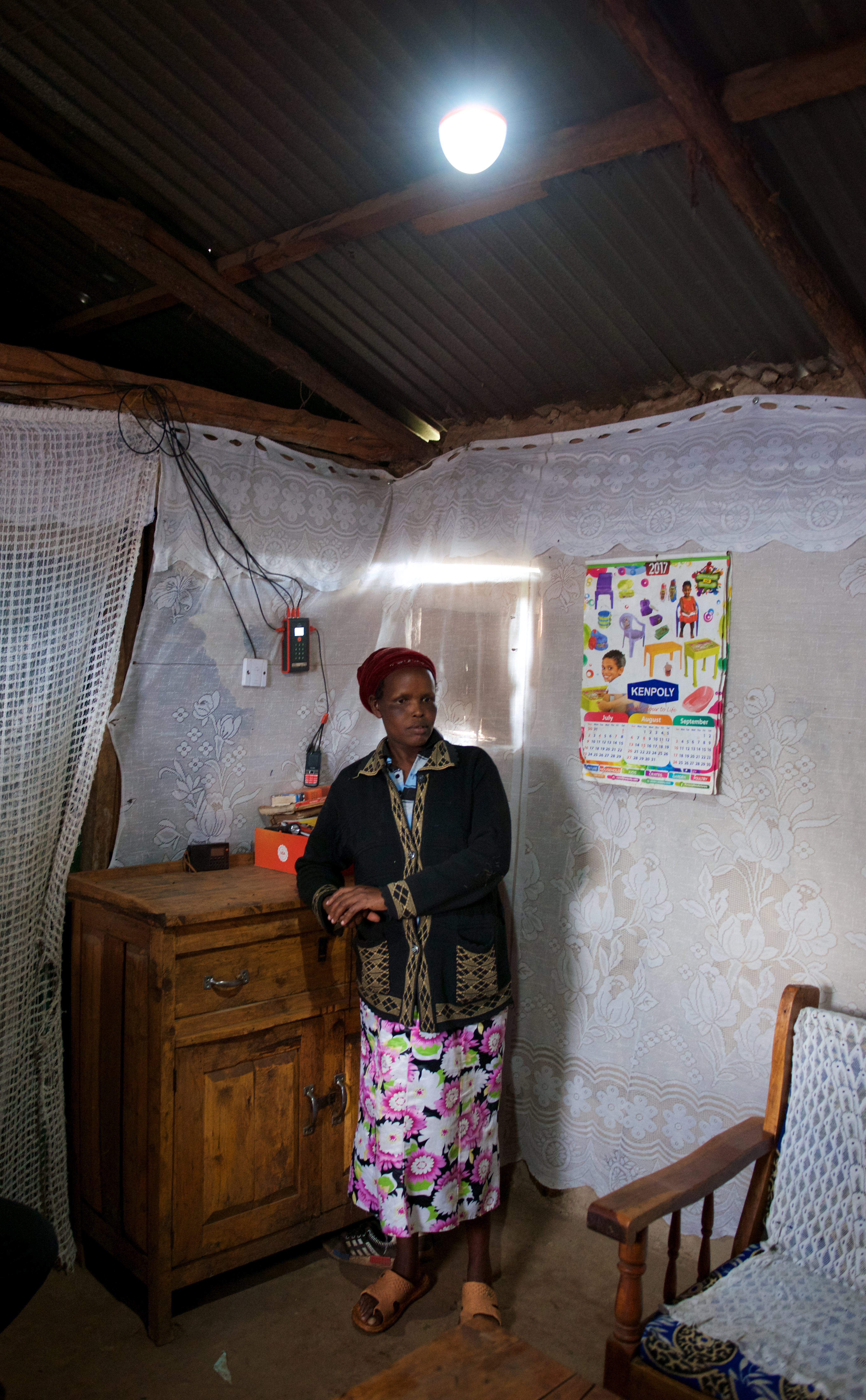 A local stands under her new solar powered lighting system