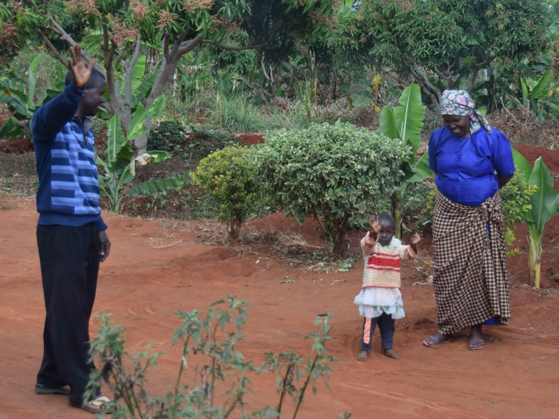 Samuel and his family stand in front of their farm, now imrpoved with solar irrigation